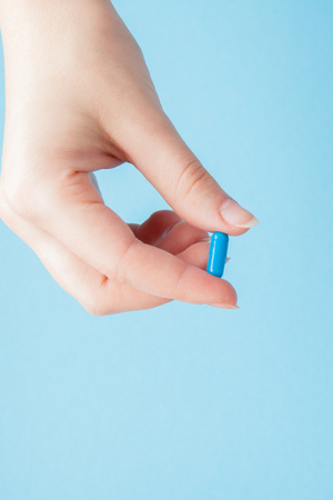 Close-up shot of pill in nurse's hand isolated over blue background. Copy space,