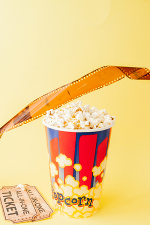 Movie tickets, film strips and popcorn on blue background. Copy space for text.