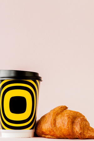 Paper cup of coffee and croissants on a pink background, Copy space