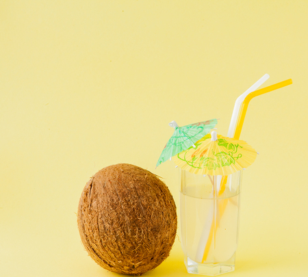 Fresh Coconut cocktail with a straws on yellow background, copy space. Stock Photo