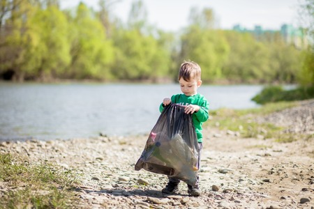 Save environment concept, a little boy collecting garbage and plastic bottles on the beach to dumped into the trash 版權商用圖片