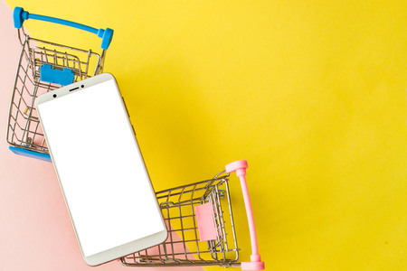 Blank screen white cellphone and shopping carts on pastel pink and yellow background. Minimal style, flatlay. Imagens
