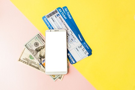 Smartphone, air ticket and dollars on pastel pink and yellow background. Minimal style, flatlay