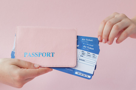 Close up tourist female horizontal hold in hand tickets for plane with orange passport, boarding pass, isolated on yellow background. Copy space advertising area. Air flight journey concept.
