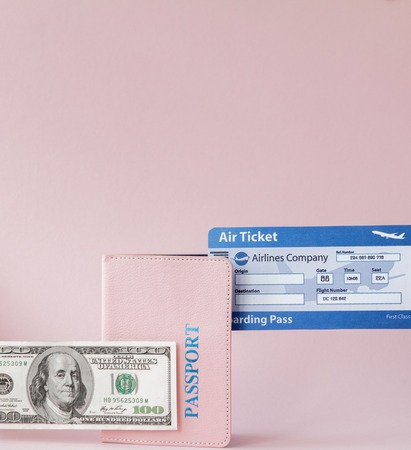 Passport, dollars and air ticket in woman hand on a pink background. Travel concept, copy space. 版權商用圖片