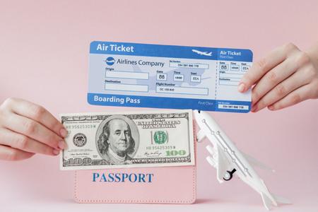 Reisepass, Dollar und Flugticket in der Hand der Frau auf rosafarbenem Hintergrund. Reisekonzept, Kopienraum.