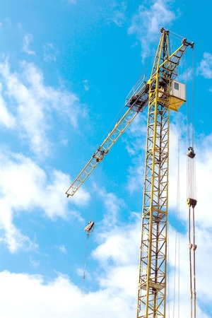 Industrial background with construction crane over blue cloudy sky.
