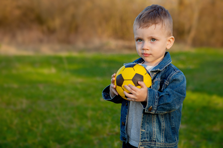 two-old years boy keeping soccer ball in park. Stockfoto