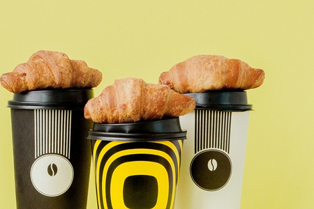 Paper cup of coffee and croissants on a yellow background 스톡 콘텐츠