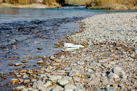 River pollution near the shore, garbage near the river, plastic food waste, contributing to pollution.