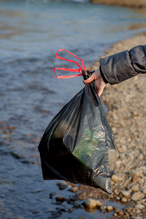 River pollution near the shore, garbage pack near the river, plastic food waste, contributing to pollution.