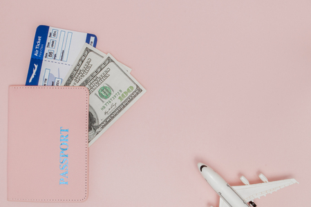 Passport, dollars, plane and air ticket on a pink background. Travel concept, copy space. Stockfoto