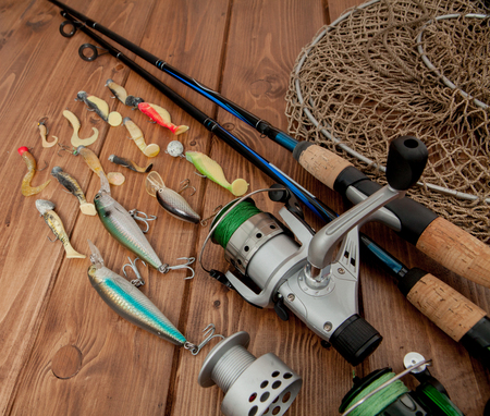 Fishing tackle - fishing spinning, hooks and lures on wooden background with copy space. Reklamní fotografie