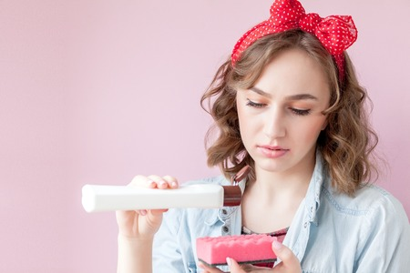 Beautiful young woman with pin-up make-up and hairstyle with cleaning tools on pink background. Imagens
