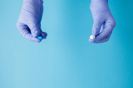 Woman hands in medical gloves giving two big pills. Blue and white. Make your selection.
