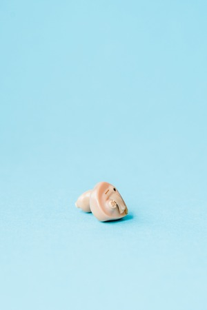 Hearing aid on blue background. Medical, pharmacy and healthcare concept. Copy space. Empty place for text or logo. Imagens