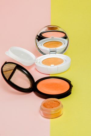 Make up products spilling on to a bright yellow and pink background with copy space, minimal style 免版税图像