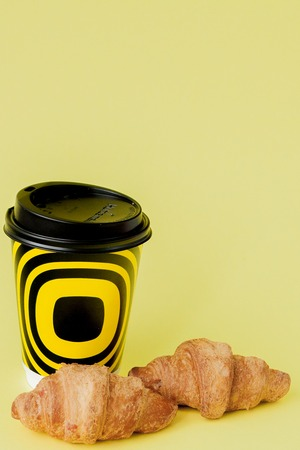 Paper cup of coffee and croissants on a yellow background, Copy space.