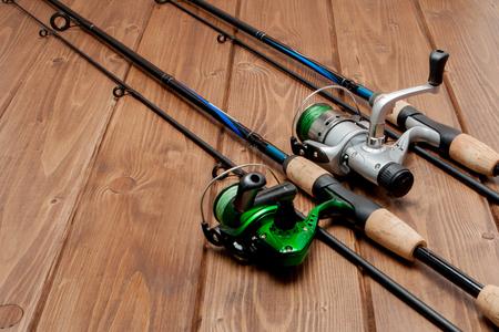 Matériel de pêche - filature de pêche, hameçons et leurres sur fond de bois avec espace de copie. Banque d'images