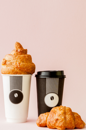 Paper cup of coffee and croissants on a pink background, Copy space 스톡 콘텐츠