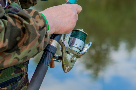 A fisherman with a fishing rod. Close-up of a hand holding a spinning rod and twisting a coil. Colorful view, blurred background, selective focus. 版權商用圖片