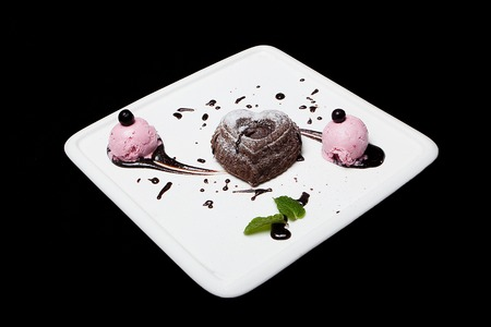 Dessert fondan chocolate with ice-cream on a white plate on a black background. Exquisite French chocolate dessert fondan, place for text.