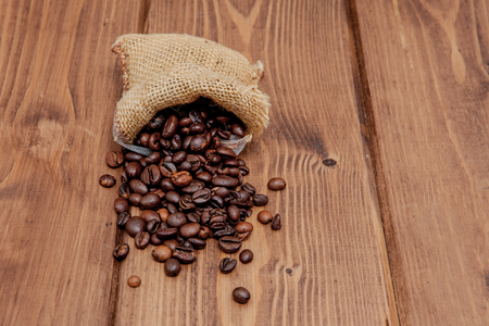 Fresh roasted coffee beans falling out the sack on the wooden surface. Brown coffee beans scattered from bag on the table