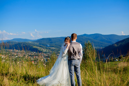 Newlyweds smile and hug each other among the meadow on top of the mountain. Wedding walk in the woods in the mountains, the gentle emotions of the couple, photo for Valentines Day. 版權商用圖片
