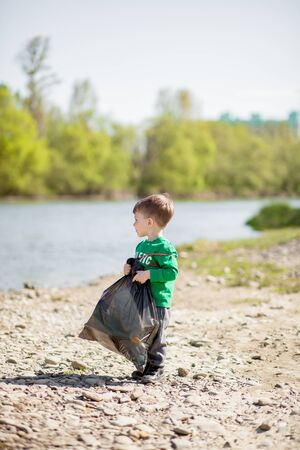 Save environment concept, a little boy collecting garbage and plastic bottles on the beach to dumped into the trash Stock Photo
