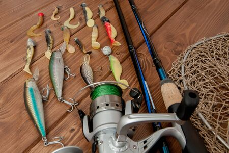 Fishing tackle - fishing spinning, hooks and lures on wooden background with copy space.