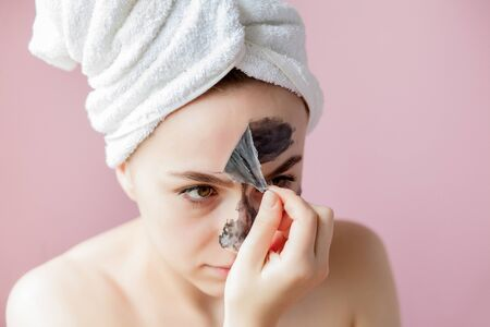 Schönheitskosmetisches Peeling. Closeup schöne junge Frau mit schwarzen Peel-Off-Maske auf der Haut. Nahaufnahme der attraktiven Frau mit kosmetischem Hautpflege-Schälprodukt auf Gesicht. Hohe Auflösung.