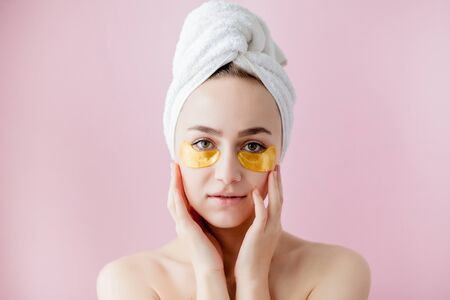 Portrait of Beauty Woman with Eye Patches on pink background. Woman Beauty Face with Mask under Eyes. Beautiful Female with natural Makeup and Gold Cosmetics Collagen Patches on Fresh Facial Skin. Standard-Bild