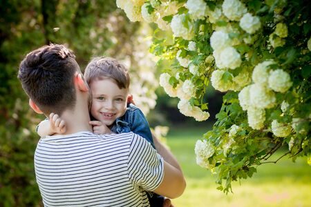 Young father and his smiling son in the park, hugging and enjoying time together, father's day celebration. Stock Photo - 137256394