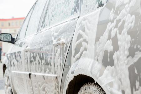 Car wash with foam in car wash station. Carwash. Washing machine at the station. Car washing concept. Car in foam. Stock Photo
