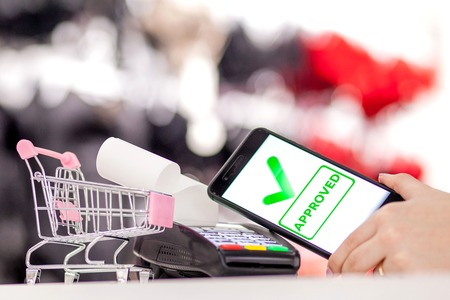 POS terminal, Payment Machine with mobile phone on store background. Contactless payment with NFC technology.