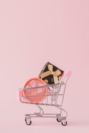Online shopping concept, shopping cart with gift boxes in pink background with copy space.
