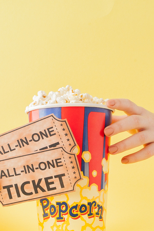 Hand takes a movie tickets and popcorn from a paper cup on a yellow background. Woman eats popcorn. Cinema Concept. Flat lay. Copy space. Stock Photo