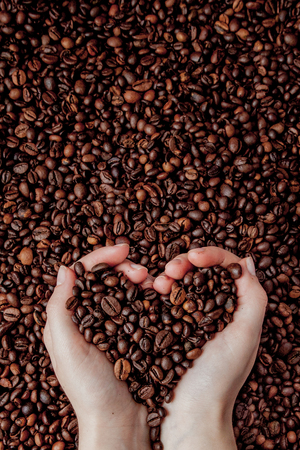 Coffee beans in man palms in form of a heart on coffee background.