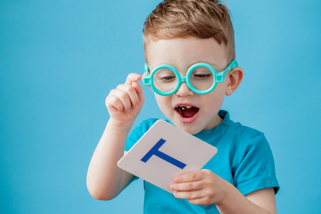 Cute little boy with letter on background. Child learn letters. Alphabet. Stock Photo