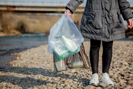 basura en la naturaleza, limpieza del medio ambiente en la primavera en el río de la basura una mujer en guantes de látex azul desechables en una bolsa de plástico azul grande.