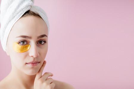 Portret van schoonheidsvrouw met ooglapjes op roze achtergrond. Vrouw schoonheid gezicht met masker onder ogen. Mooie vrouw met natuurlijke make-up en gouden cosmetica collageen patches op frisse gezichtshuid. Stockfoto