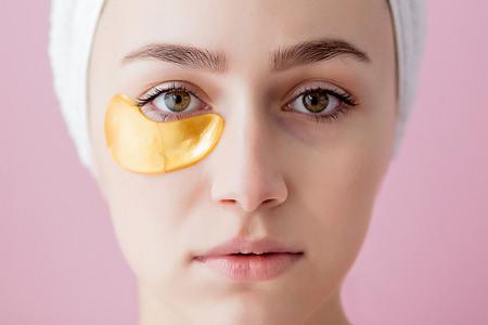 Porträt der Schönheits-Frau mit Augenklappen auf rosa Hintergrund. Frauen-Schönheits-Gesicht mit Maske unter Augen. Schöne Frau mit natürlichem Make-up und Goldkosmetik-Kollagen-Patches auf frischer Gesichtshaut.