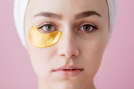 Portrait of Beauty Woman with Eye Patches on pink background. Woman Beauty Face with Mask under Eyes. Beautiful Female with natural Makeup and Gold Cosmetics Collagen Patches on Fresh Facial Skin.