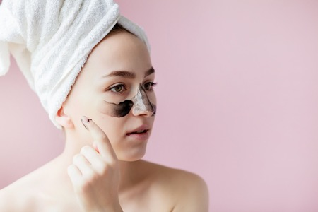 Beauty Cosmetic Peeling. Closeup Beautiful Young Female With Black Peel Off Mask On Skin. Closeup Of Attractive Woman With Cosmetic Skin Care Peeling Product On Face. High Resolution. Stockfoto