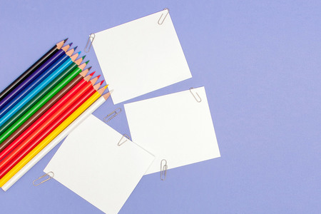 Blanks sheet of papers and color pencils on violet background for Projects and Announcements, copy space. Фото со стока