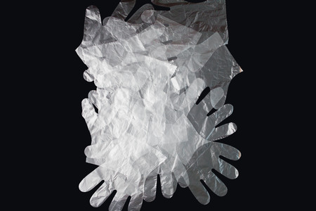 Plastic bag with handles, gloves, on a black background . Used plastic bag for recycling. Concept - ecology, planet pollution with plastic cellophane polyethylene. Banco de Imagens