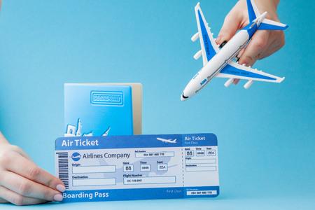 Pasaporte, avión y boleto aéreo en mano de mujer sobre un fondo azul. Concepto de viaje, espacio de copia.