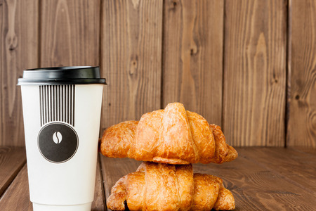 Paper coffee cup and croissants on wooden background, Copy space.
