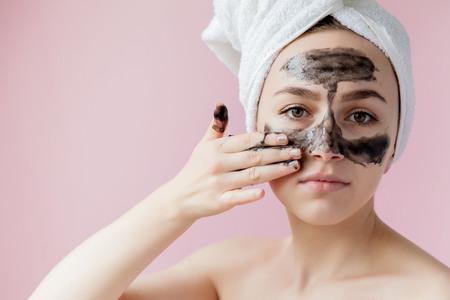 Peeling cosmético de belleza. Closeup hermosa mujer joven con máscara negra Peel Off en la piel. Primer plano de una mujer atractiva con el producto de peeling cosmético para el cuidado de la piel en la cara. Alta resolución.