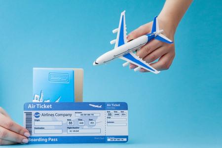 Reisepass, Flugzeug und Flugticket in der Hand der Frau auf blauem Hintergrund. Reisekonzept, Kopienraum.